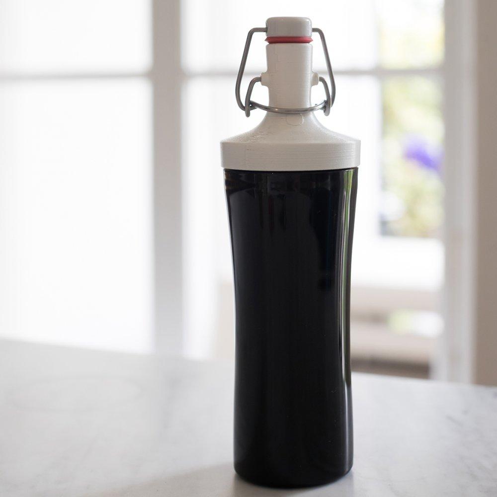 Wiederverwendbare schwarze, große Koziol Plopp to-go Flasche stehend auf einer hellen Theke