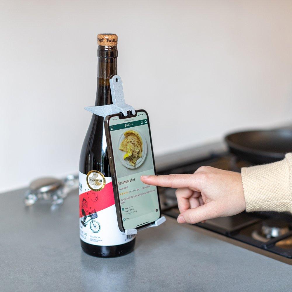 Smartphonehalterbefestigt an Weinflasche als Rezeptehalter stehend neben dem Herd