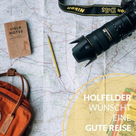 Landkarte mit Rücksack, Kamera Notitzbuch und Bleistift