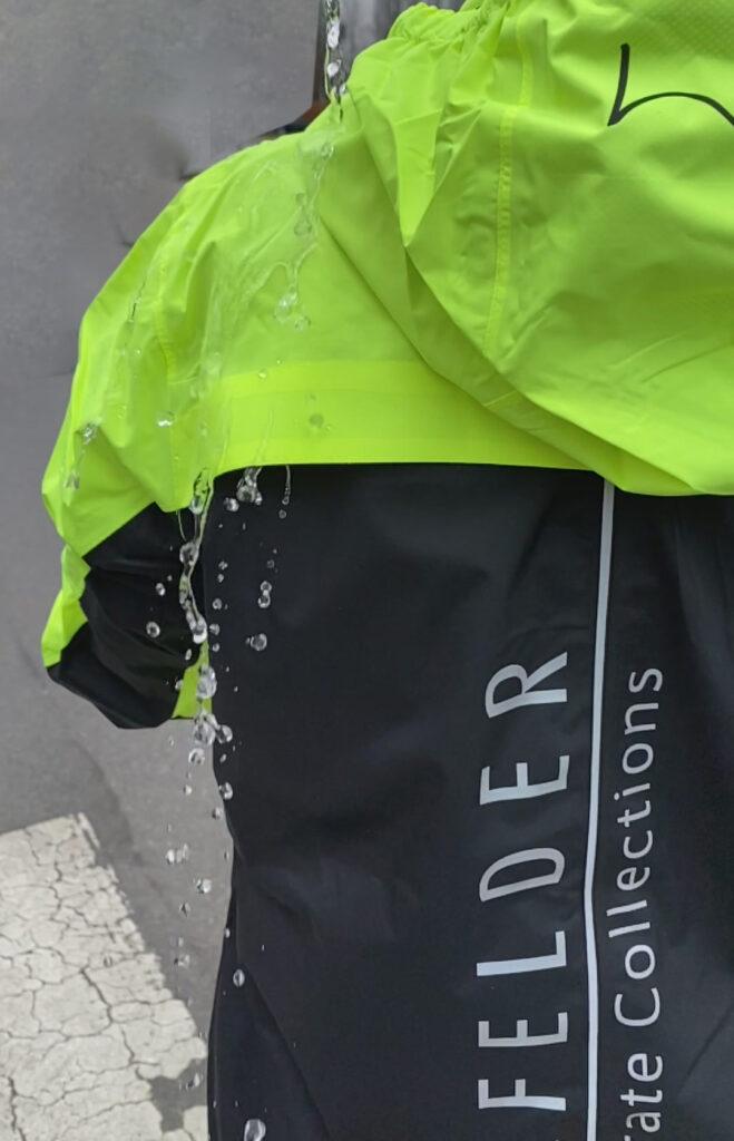 Wasser prasselt von Funktions-Jacke ab; reflektierendes Logo auf Rücken. Sicher Unterwegs